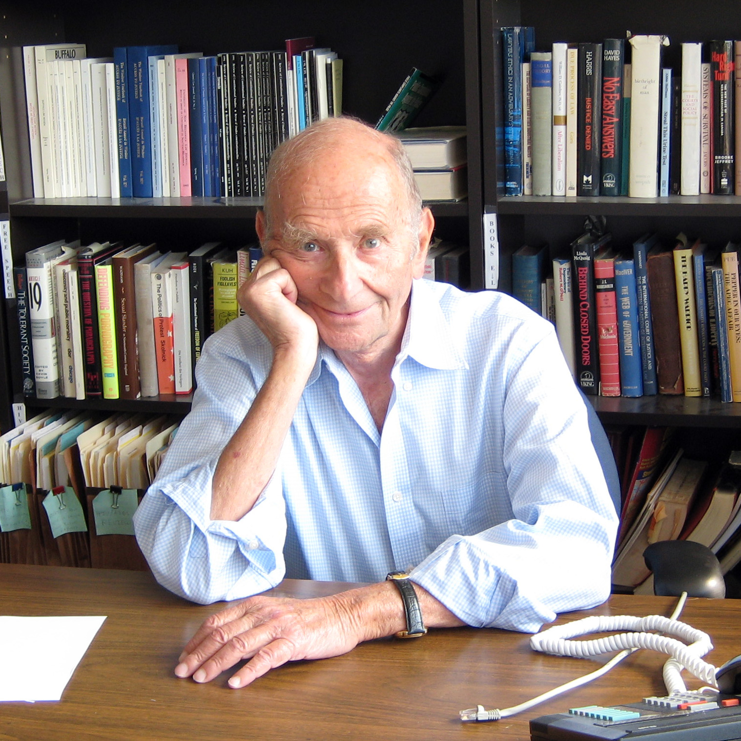 Alan Borovoy sitting at his desk with many books in the background. He is smiling and is leaning his right cheek against his hand.