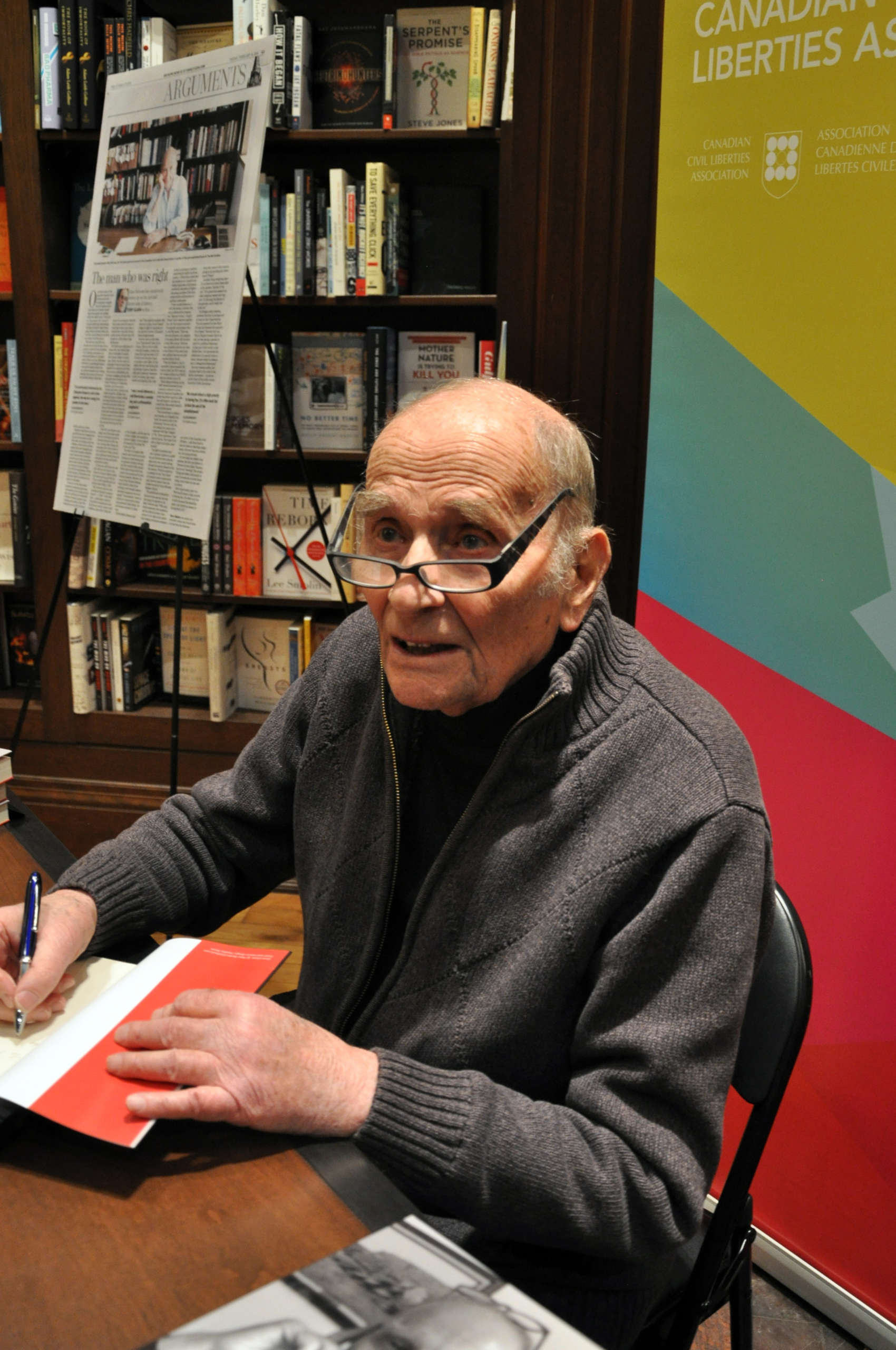 A Alan Borovoy signs books at a table at Ben McNalley's book store. He is wearing glasses and a grey zip up sweater. In the background are a poster of a feature on him in the Toronto Star, and a stand-up banner for the Canadian Civil Liberties Association.