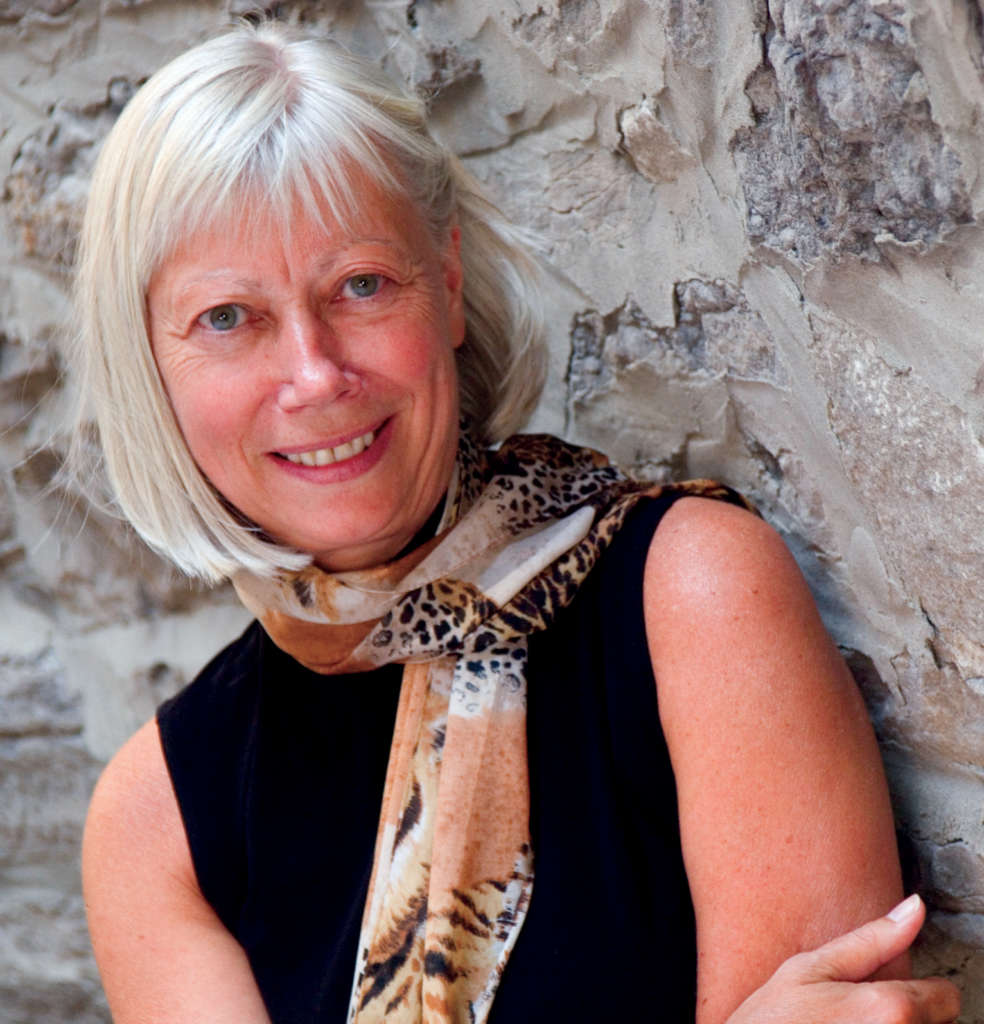 Author Constance Backhouse standing outdoors by a concrete wall. She is wearing a black dress with a leopard print scarf and smiling.