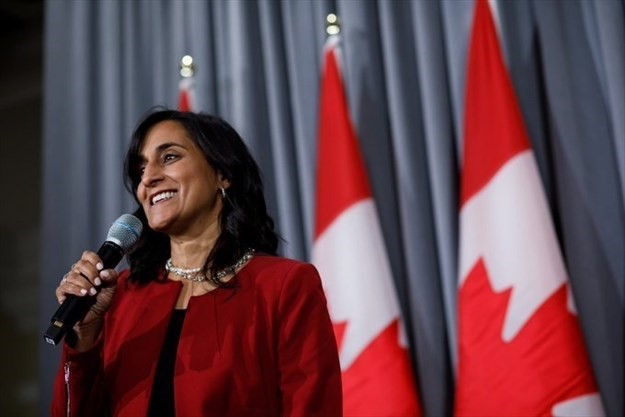 Anita Indira Anand delivers a speech and smiling. She has a medium skin tone and is wearing a red blazer and a pearl necklace. Three Canadian flags stand in the background.