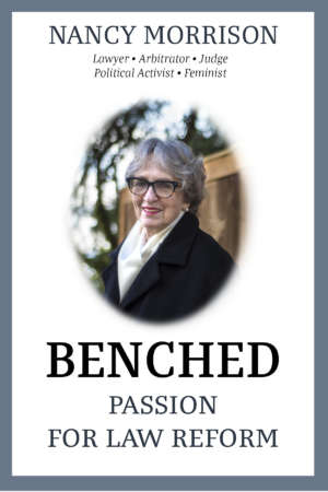 Book cover for Benched: Passion for Law Reform by Nancy Morrison. The cover shows a photo of Nancy in the centre, smiling and wearing large tortoiseshell glasses, a black coat and a beige scarf.