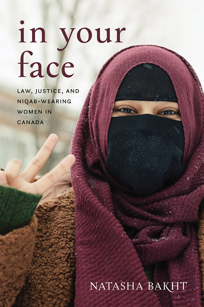 Book cover for In Your Face: Law, Justice, and Niqab-Wearing Women in Canada by Natasha Bakht. The cover shows a woman wearing a niqab face covering. Her eyes are smiling and her fingers are forming a peace sign.